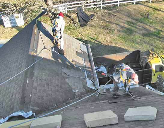 Workers harnessed on a roof