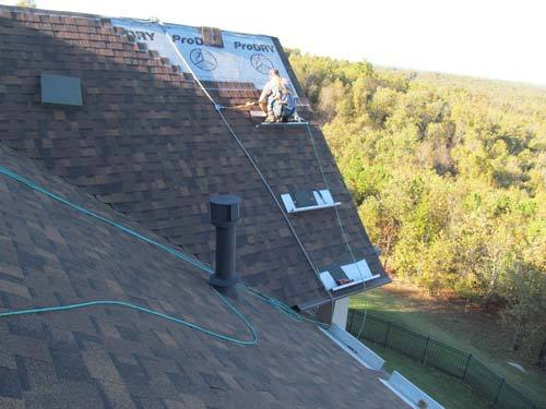 Worker about to finish applying shingles to a side of the roof