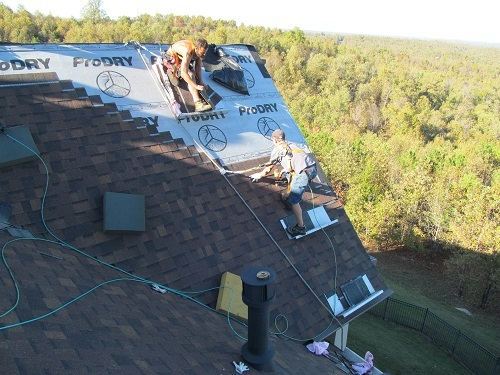 Barnes Roofing roof safety - Two workers applying shingles on a roof